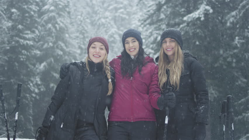 Portrait shot of three young ladies embracing, and smiling at the camera on a snowy day | Shutterstock HD Video #25753355