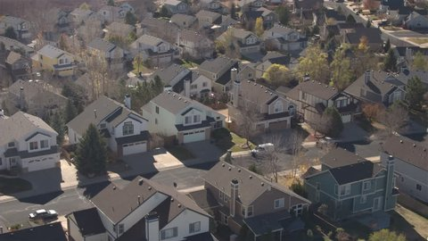 AERIAL, CLOSE UP: Flying close above the rooftops of beautiful idyllic wooden row house in subdivision suburban town. Parallel streets with turning fall foliage tree avenue in idyllic quiet sunny city