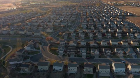AERIAL: Flying above the rooftops of modern expensive row houses in subdivision housing town, Denver, America. Roundabout, streets and driveways in luxury quiet suburban community on sunny morning