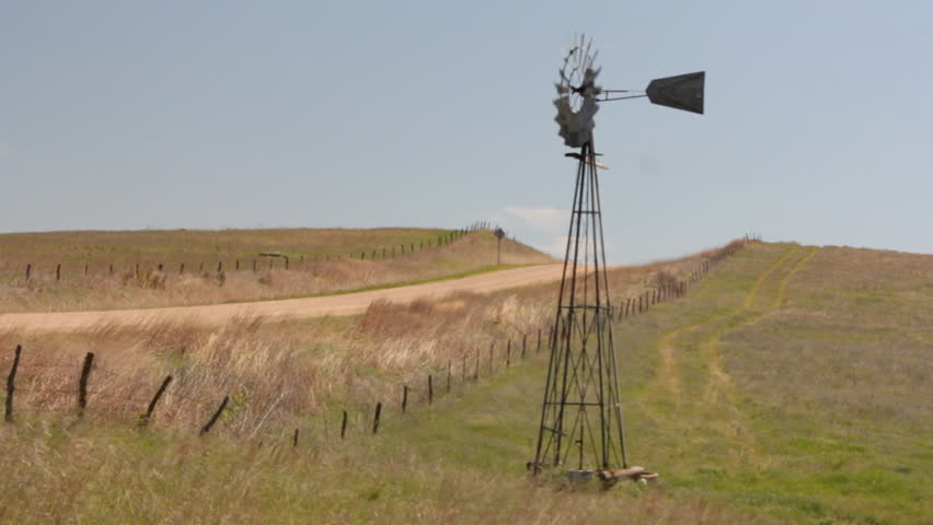 A windmill out in the Kansas Prairie pumping water for the cows on a windy day.