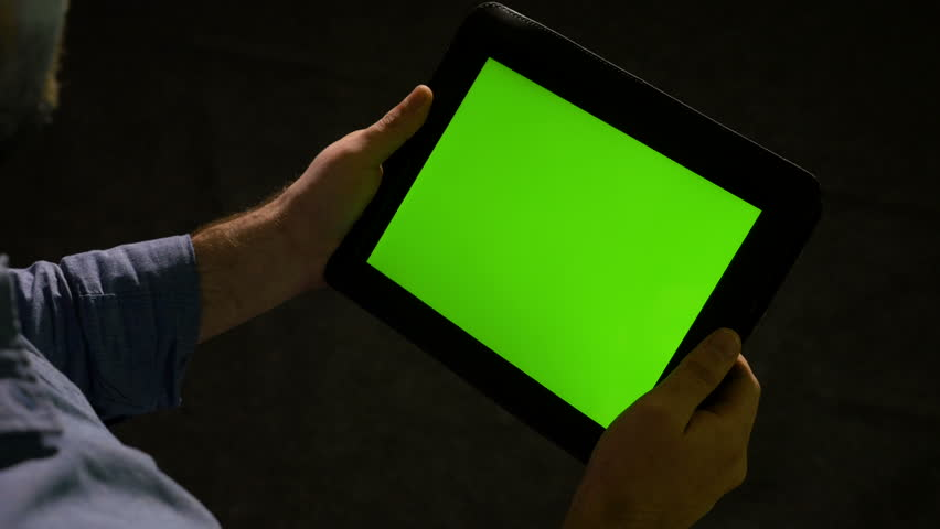 Man using tablet pc with green screen and zooming in and out on the display