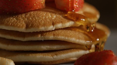 Maple syrup drizzled over stacked pancakes and strawberries