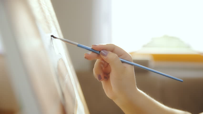Dolly slide canvas from side while artist painting 4K. Long shot close up on person hand in focus holding paint brush and painting on canvas. Window bright light in background shining. | Shutterstock HD Video #25801520
