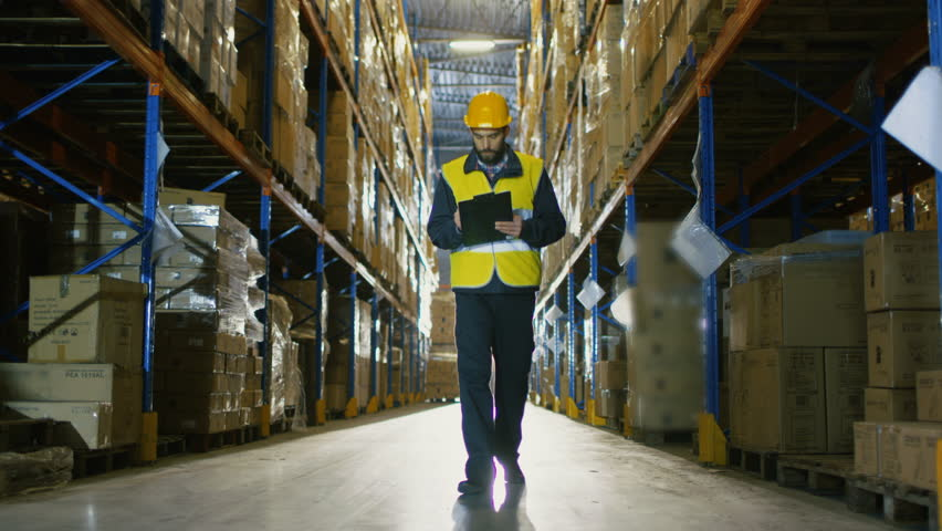 Overseer Wearing Hard Hat with Tablet Computer Counts Merchandise in Warehouse. He Walks Through Rows of Storage Racks with Merchandise. Shot on RED EPIC-W 8K Helium Cinema Camera.
