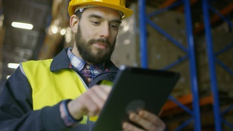 Surveyor Wearing Hard Hat Holds Tablet Computer and Counts Merchandise in Warehouse full of Racks with Boxes on Them.