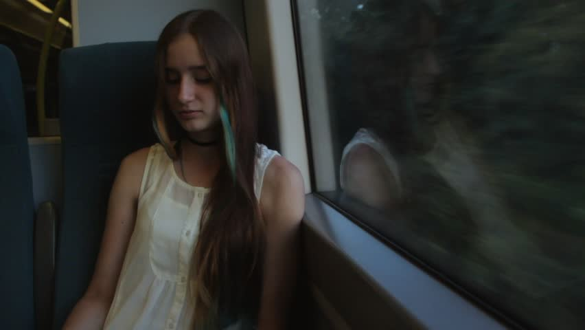 Young brunette beautiful hipster girl with long hair unravels the headphones, sitting by the window in the train. | Shutterstock HD Video #25823540