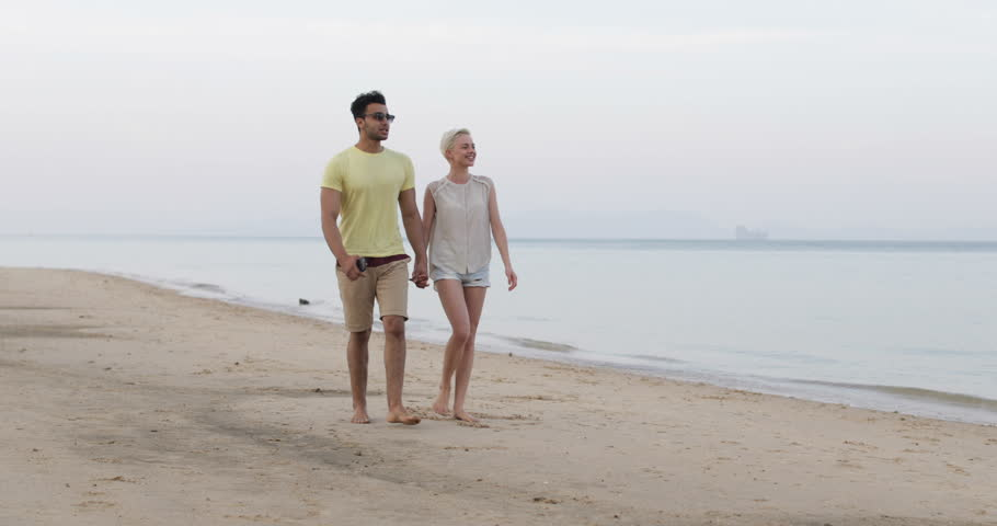 Couple Walking On Beach Holding Hands Talking, Hispanic Man And Young Woman Point Finger, Tourists Vacation Slow Motion 60   Shutterstock HD Video #25827680