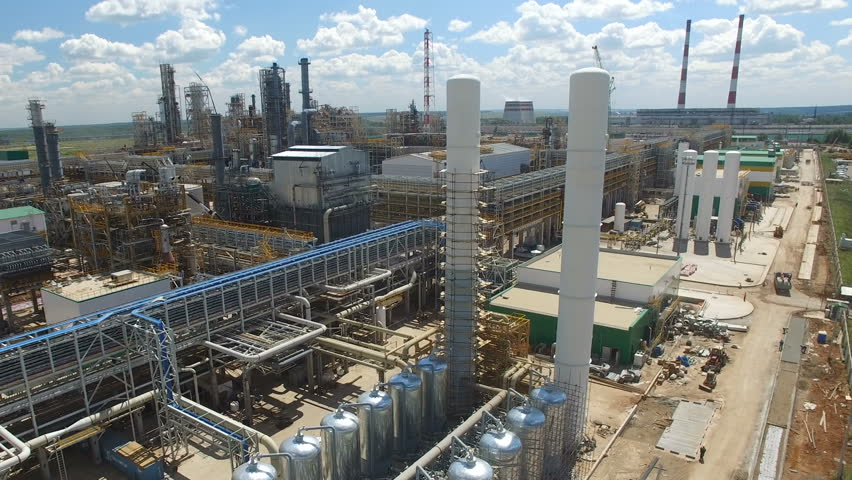 drone flies over large metal tanks lines and high towers on oil refinery plant territory against sky with white clouds