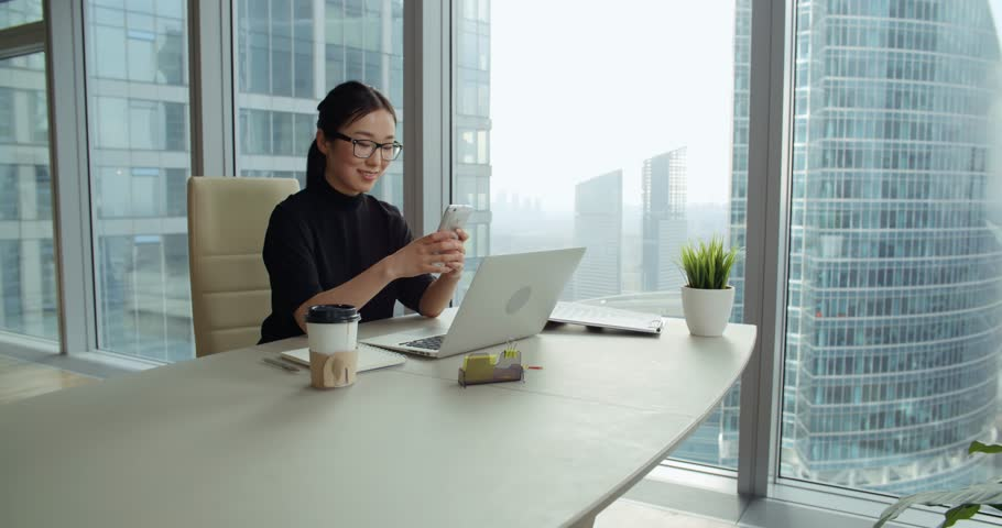 Successful young asian girl in a modern office skyscraper the work young business asian girl texting on smartphone in office 4k stock video clip sciox Choice Image