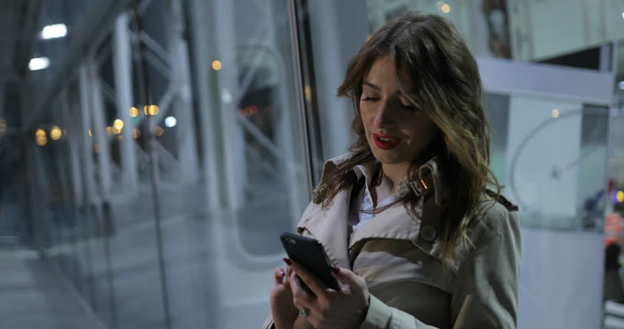 Charming woman is typing on a phone, outdoors in the city at night. | Shutterstock HD Video #25833230