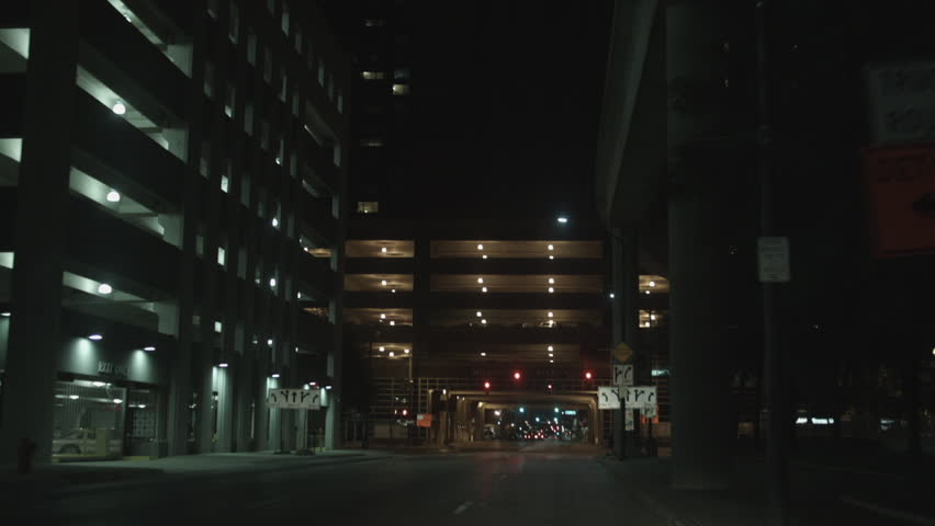 DETROIT, MI - CIRCA 2014: Driving plate: front view. On Congress Avenue in down town at night past high-rise commercial property and parking structures.  Mid West USA, overcast. 24mm lens, stabilized