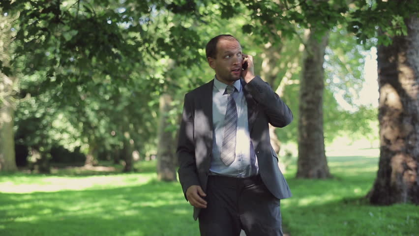 Businessman receiving phone call during jogging in park