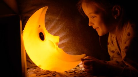 The child falls asleep under a lamp.