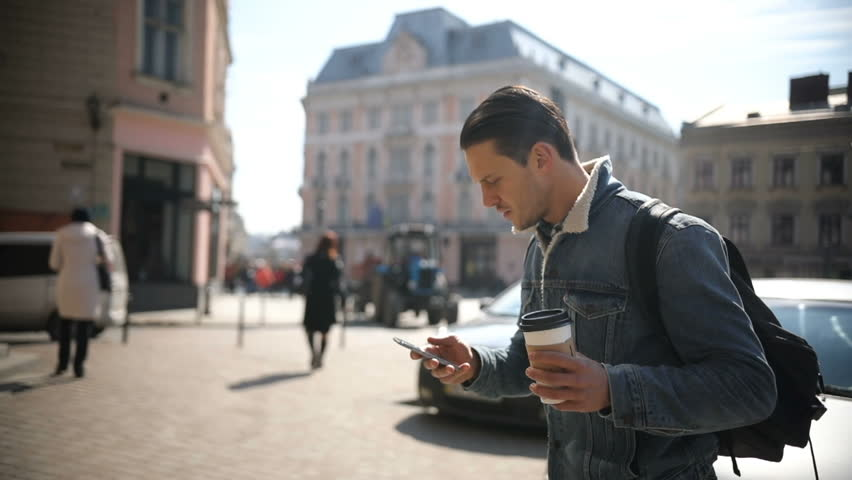 Young attractive man walks down the street holding coffee and using phone | Shutterstock HD Video #25902515
