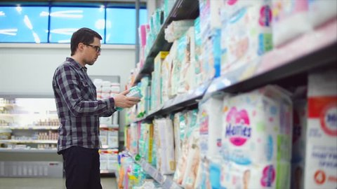 A serious man in glasses, dressed in a plaid shirt examines diapers in the children's department of the hypermarket. A person considers children's belongings for his little child.