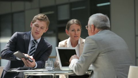 Business people sitting down at table and starting the discussion