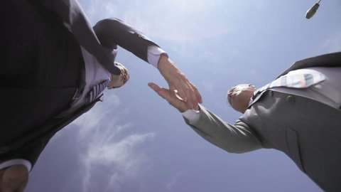 Businessmen of different age viewed from below shaking hands and talking