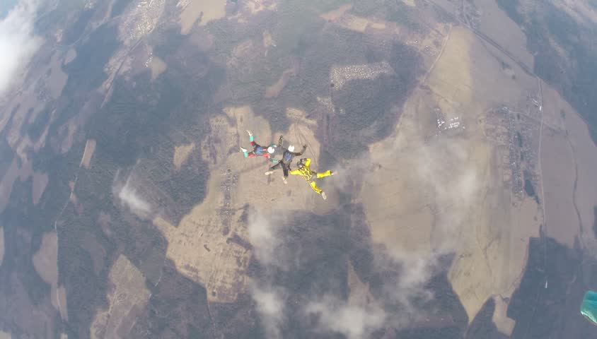 Three skydivers are training in the sky. #25947950