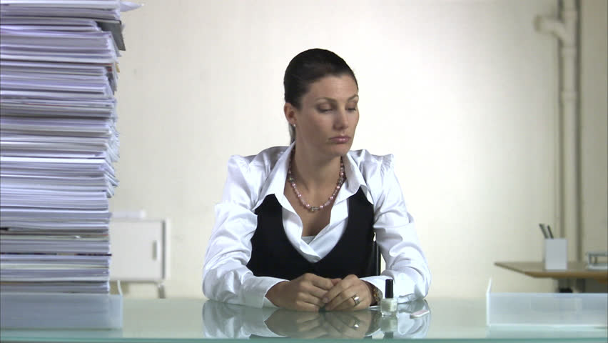 A woman sitting in an office polishing her nails when a pile of paper next to her grows higher