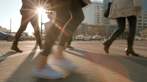 Young Lady in a coat and white sneakers is crossing the road with People from the Crowd at a Pedestrian Crossing in Sunny Weather