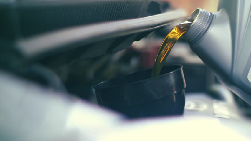 Pouring fresh new clean synthetic oil into car's engine, closeup. 4K UHD slow, motion.