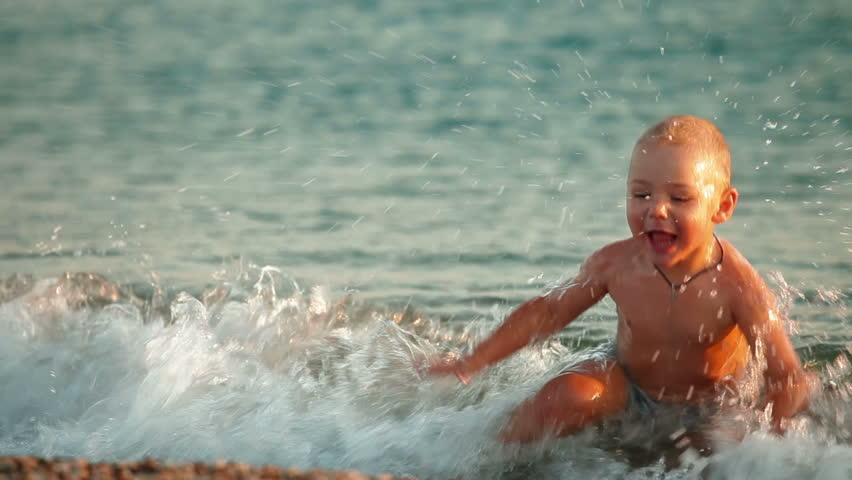 Happy kid splashing in the surf on a summer beach