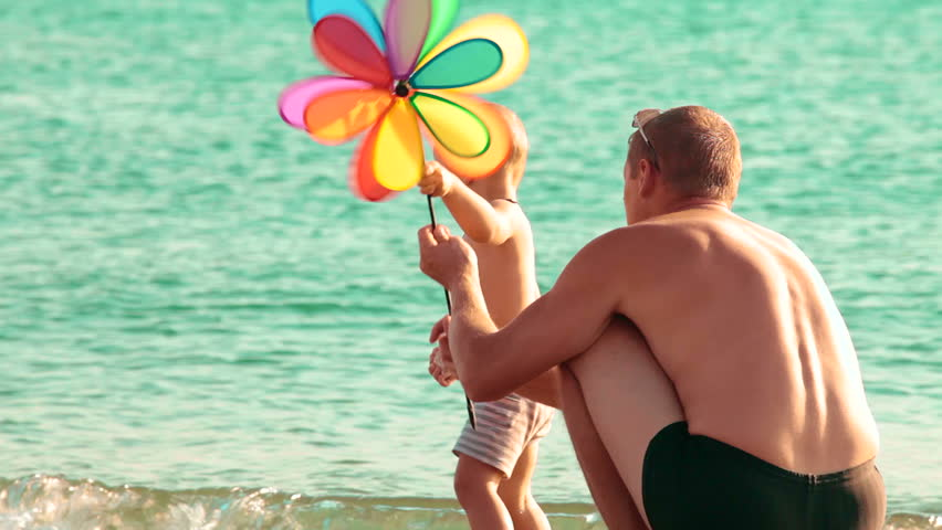 The father with kid resting on a summer beach