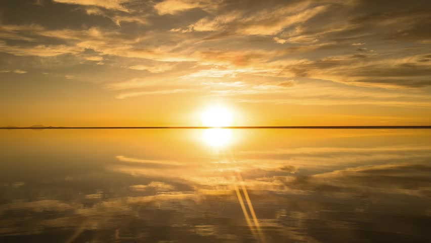 Time-lapse of the beautiful sunset and moving cloud, sun eventually sink under the horizon, all reflected on the water in Salar de Uyuni, Bolivia, South America.