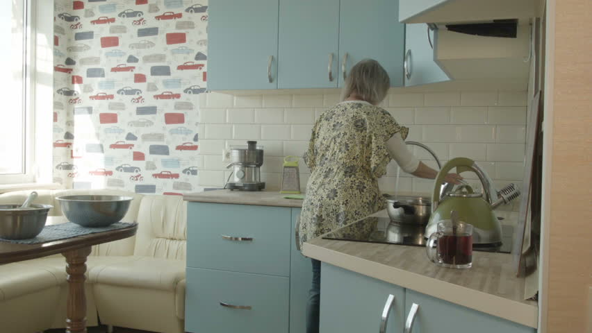 An elderly woman washes dishes in the kitchen, cleans the room, erases from the table. The housewife cleans up the kitchen.
