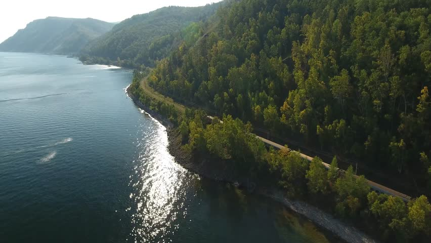 Lake Baikal oldest. Railways Russia Siberia. listvyanka. Passenger train rides near the water behind trees rzd. Mountains pine forest summer sun shines blue water. Beautiful aerial follow above lake