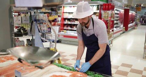 Fishmonger in store arranging fish counter