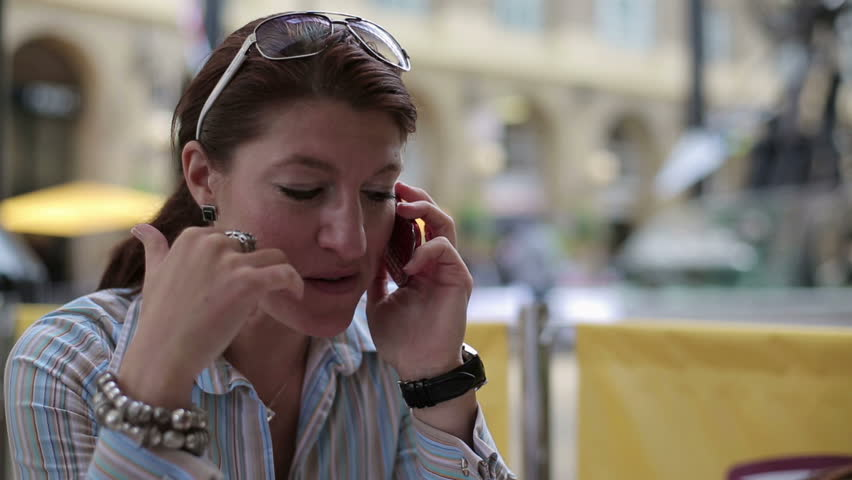Woman talking on cellphone and eating in the city - HD stock footage clip