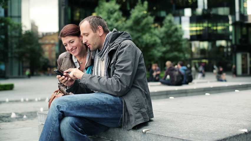 Happy couple with smartphone in the city