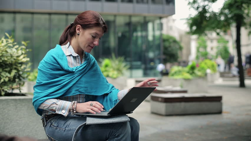 Young happy woman with modern laptop in the city HD - HD stock video clip