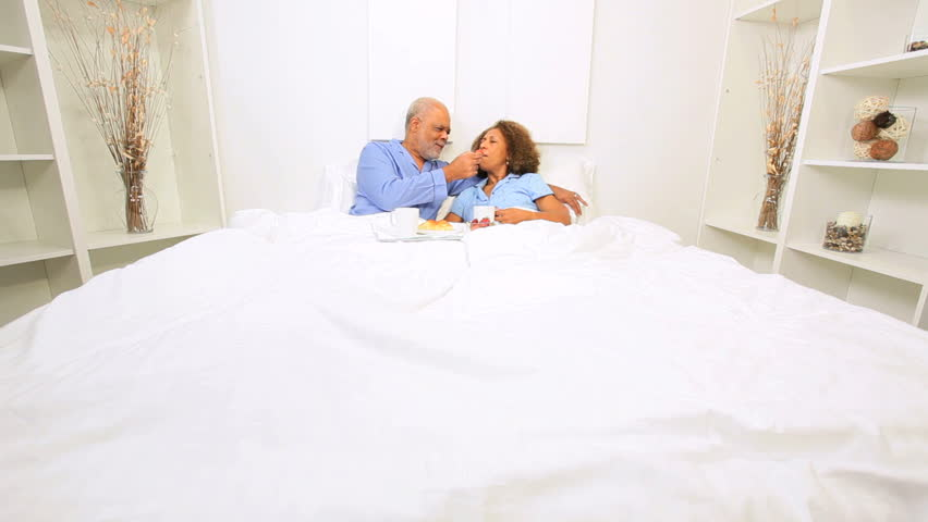 Elderly ethnic heterosexual couple enjoying eating breakfast bedroom home