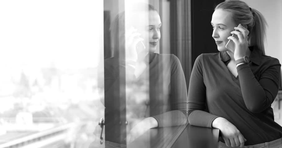 Elegant Woman Using Mobile Phone by window in office building | Shutterstock HD Video #26012360