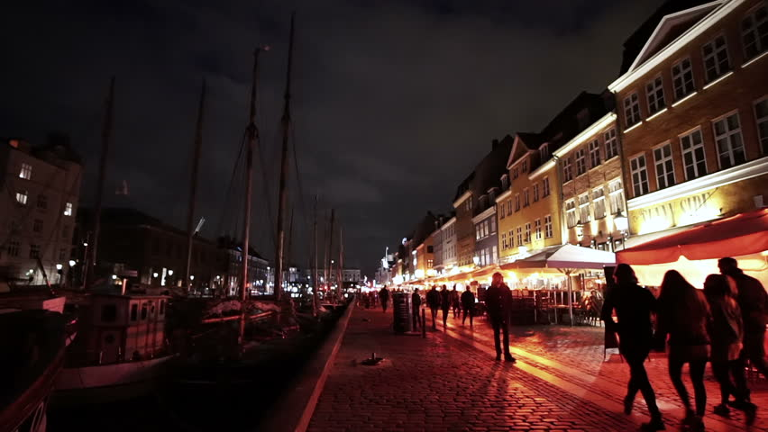 Copenhagen, Denmark - April 2017: Night video of people, tourist walking at Nyhavn landmark area with bars and restaurants