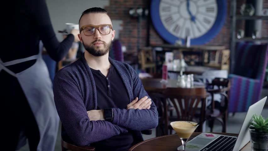 Portrait of an attractive young man in glasses. Hipster in casual clothes looks into the camera with a slight smile. Actually looks guy   Shutterstock HD Video #26030810