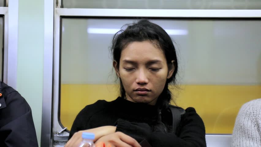A sleepy girl is on the train. A young woman is asleep in a subway. Tired traveler sitting on a metro train. | Shutterstock HD Video #26065640