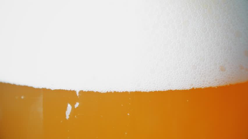 White foam sliding down of beer glass. 4k UltraHD video #26068730