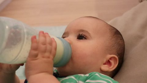 Close up of a few month old baby drinking milk formula from a bottle