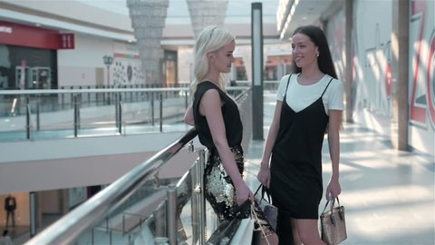 Two girl-friends on shopping has risen on the escalator with bags, fashion woman shopping
