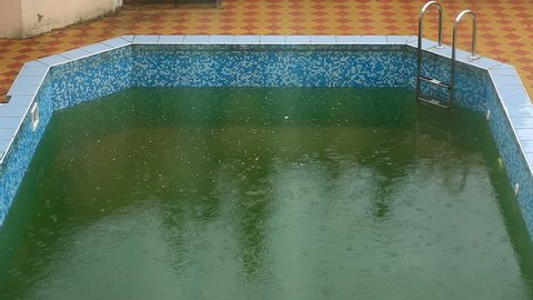 Heavy rain falls into a swimming pool. Not season, dirty abandoned pool