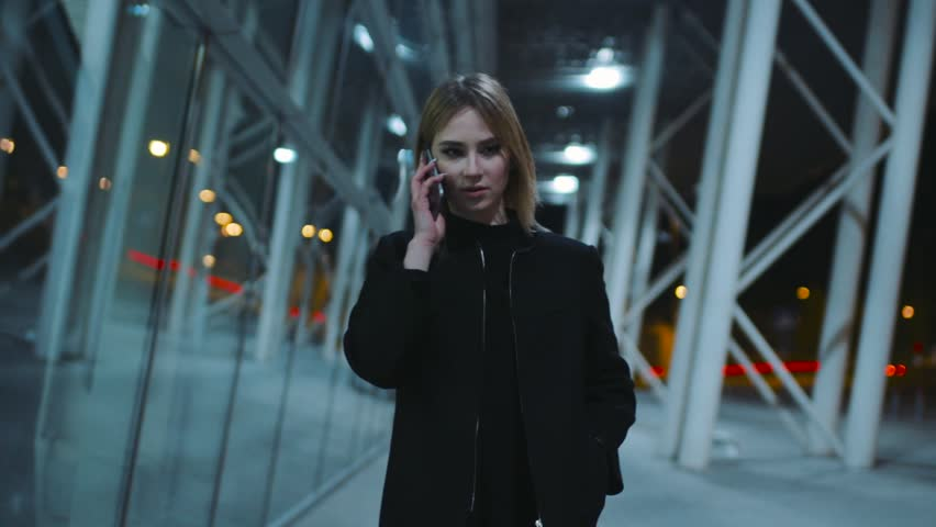 Charming young woman in a good mood in the dark clothes is near the business center in the evening. The girl is talking with someone on her smartphone. Evening in the city, good mood.   Shutterstock HD Video #26112950