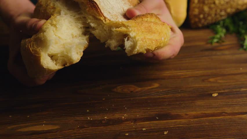 Baker man hands tearing fresh bread on a half. Male hands breaking whole grain bread. Close up view.