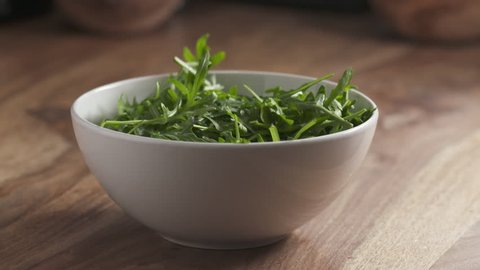 Slow motion of washed arugula leaves falling into the bowl on wooden table, 180fps prores footage