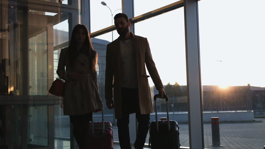 Beautiful young couple goes to the frame of the luggage at the airport sunset