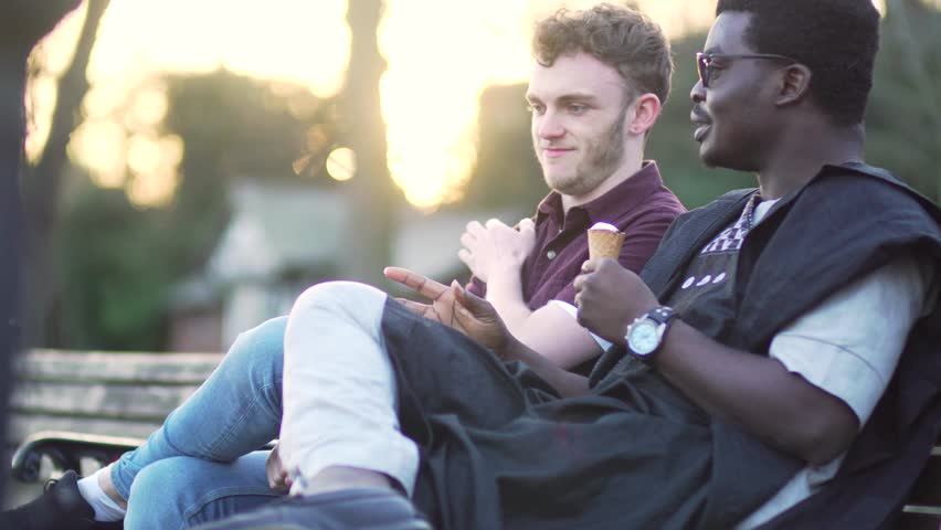 Two men happy friends / gay talking and eating ice cream at sunset, sitting  laughing and smiling. Young handsome males multi-ethnic diversity, ...