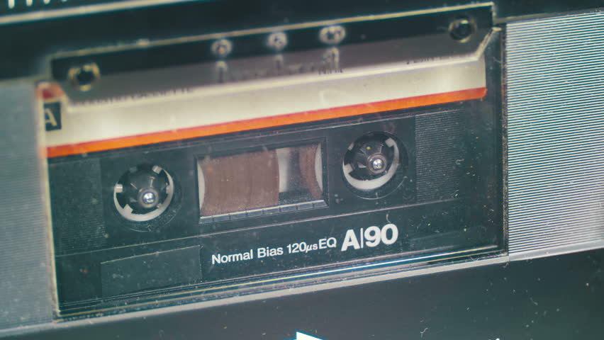 Vintage Audio Tape with White Blank Label is Rotates. Audio Tape. Macro static camera view of vintage audio cassette tape with a blank white label in use sound recording in a cassette player.