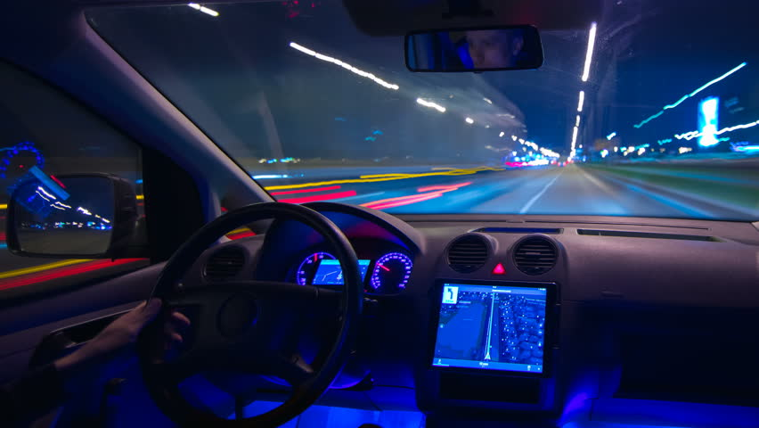 The man drive a car in the night city with a gps. inside view. hyperlapse